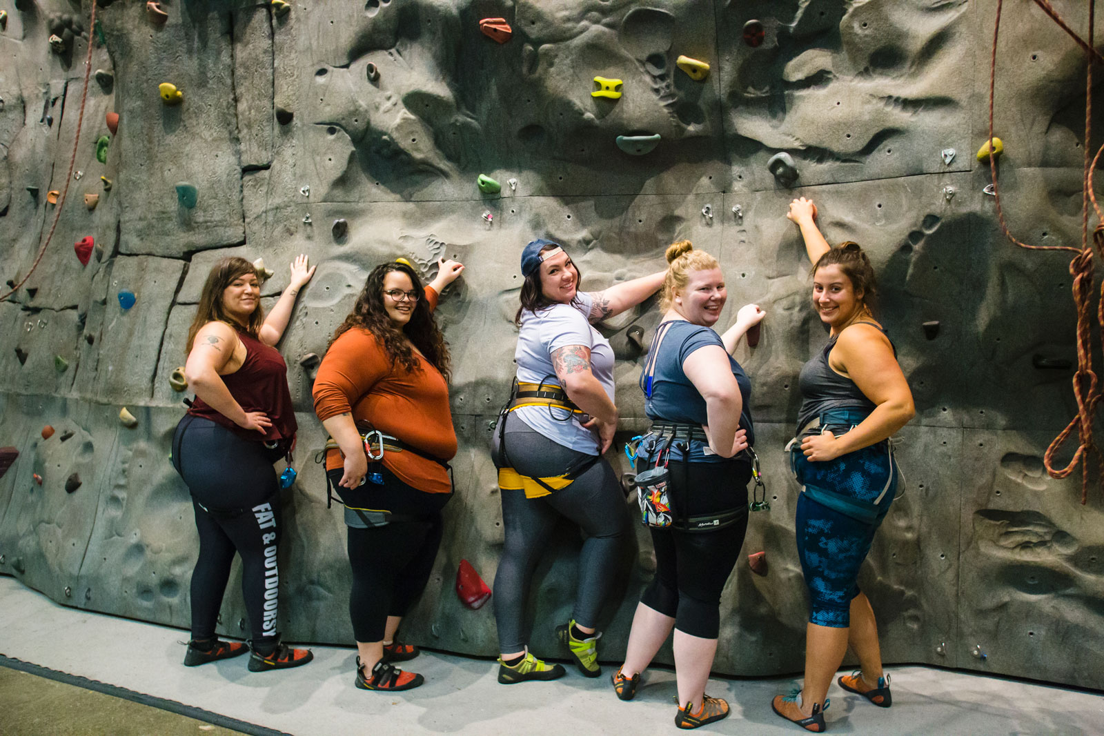 5 fat women standing by a rock wall